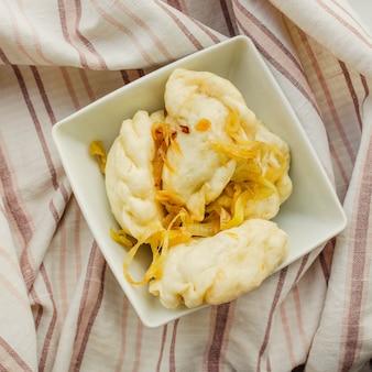 감자와 함께 러시아 음식 vareniki가 그릇에 제공됩니다.