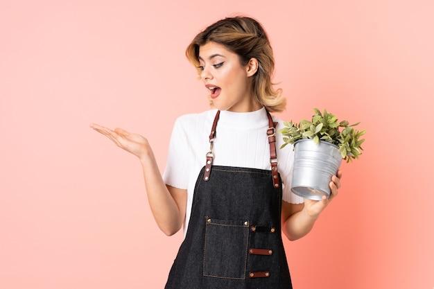 Русская девушка-садовник держит растение, изолированное на розовом, держит воображаемую копию пространства на ладони