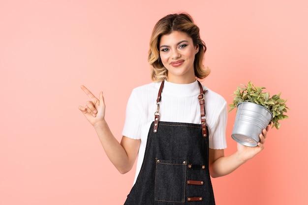 Русский садовник девушка держит растение изолированно на розовом указывая пальцем в сторону