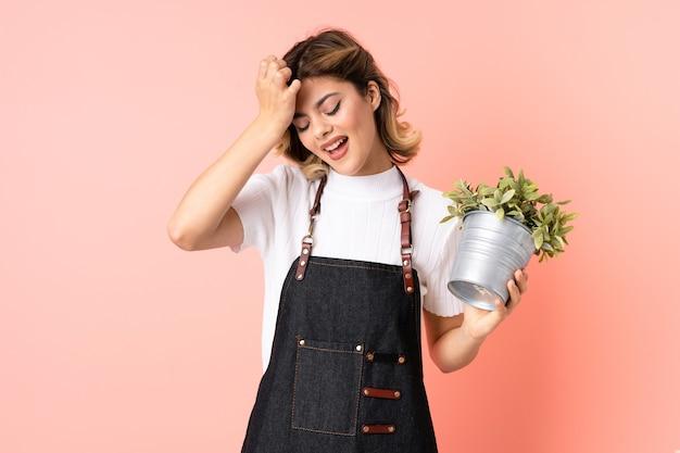 混乱した表情に疑問を持っているピンクの壁に隔離された植物を保持しているロシアの庭師の女の子