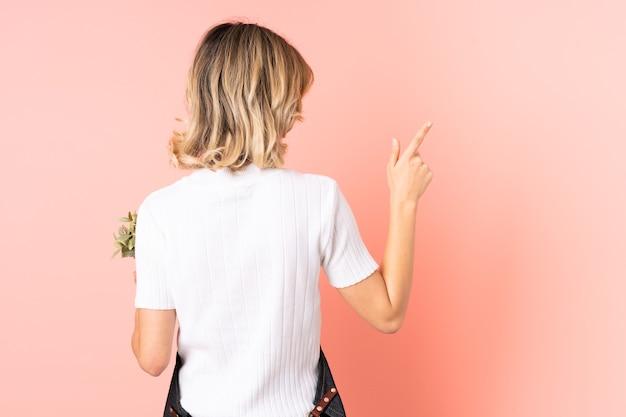 人差し指で後ろ向きのピンクの壁に分離された植物を保持しているロシアの庭師の女の子