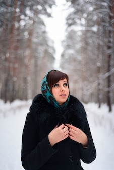 Russian girl in coat and scarf in cold winter
