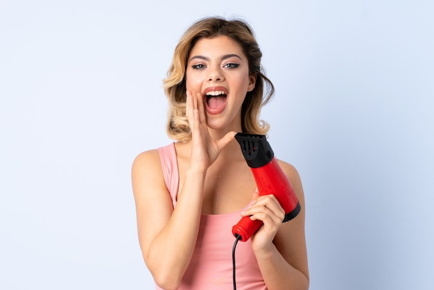 Russian girl holding a hairdryer isolated on blue shouting with mouth wide open
