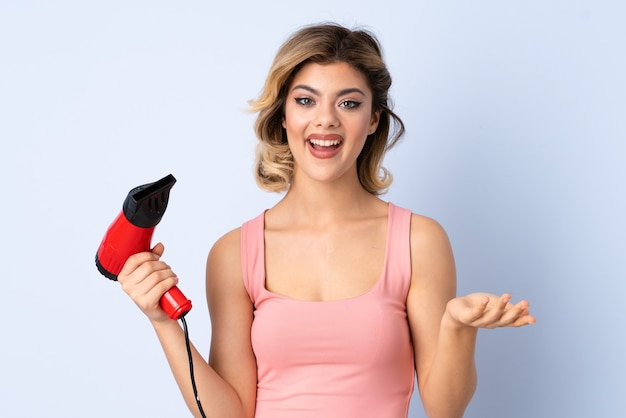 Russian girl holding a hairdryer isolated on blue with shocked facial expression