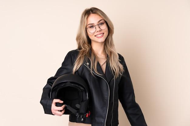 Русская девушка в мотоциклетном шлеме изолирована на бежевом в очках и улыбается