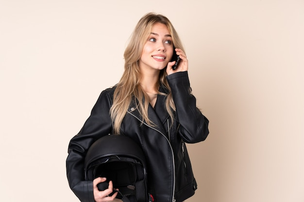 Russian girl with a motorcycle helmet isolated on beige wall keeping a conversation with the mobile phone with someone