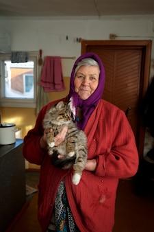 Русская бабушка держит на руках котенка, деревня, сибирь, зима.
