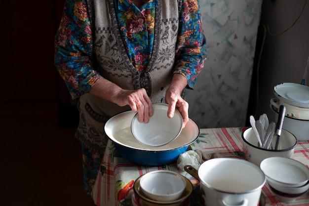 Русская бабушка моет посуду в тазике в деревне.