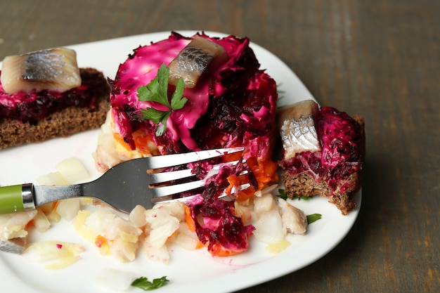 Салат из русской сельди на тарелке после застолья, на деревянном столе