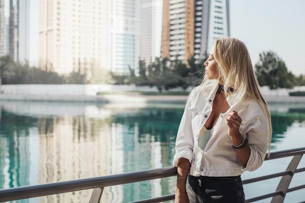 건물 주변의 푸른 깨끗한 호수가 내려다 보이는 두바이 라이프 스타일의 도시 도시를 여행하는 러시아 아가씨. 라이프 스타일 잡지 및 관광 명소에 대한 금발 아가씨의 도시 생활 사진.