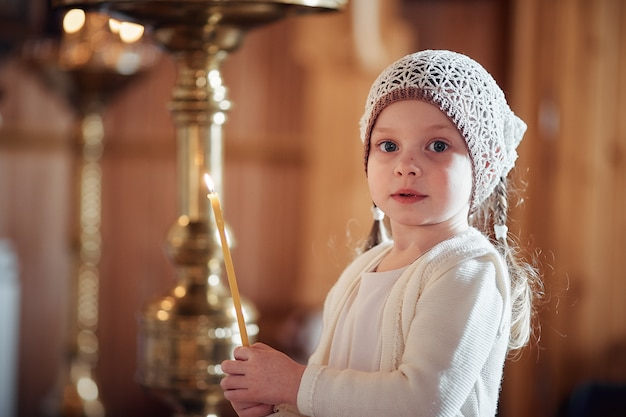 Russian little girl in a scarf on her head stands in an orthodox church
