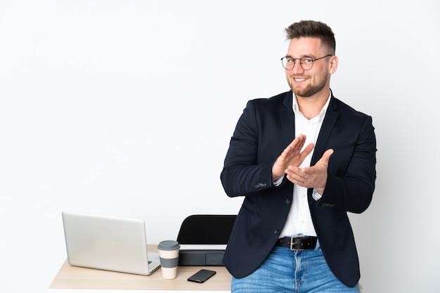 Русский человек в кабинете на белой стене аплодирует после презентации на конференции