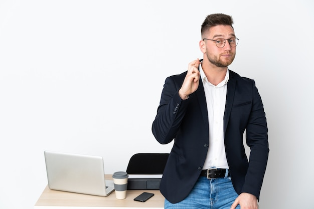 Русский человек в офисе на белой стене с пальцами скрещивания и желая лучшего