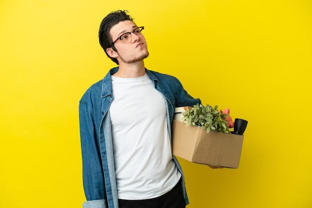 Русский мужчина делает движение, поднимая коробку, полную вещей, изолированную на желтом фоне, и смотрит вверх
