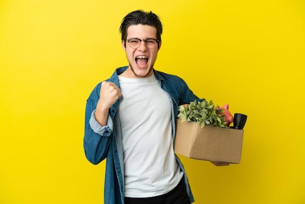 Русский мужчина делает ход, поднимая коробку, полную вещей, изолированную на желтом фоне, празднует победу в позиции победителя