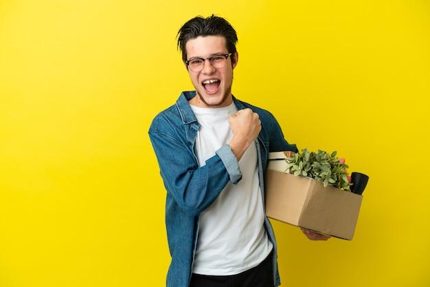Русский мужчина делает движение, поднимая коробку, полную вещей, изолированную на желтом фоне, празднуя победу