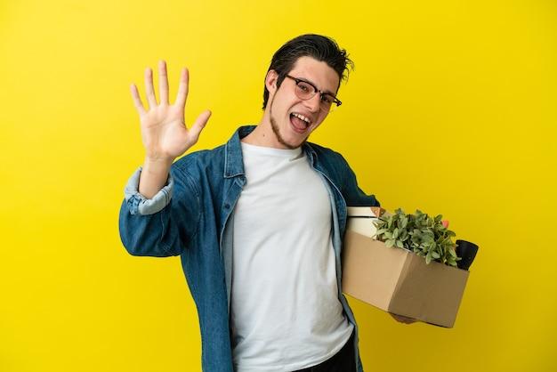 Русский мужчина делает движение, поднимая коробку, полную вещей, изолированную на желтом фоне, считая пять пальцами