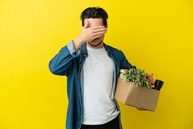 Русский мужчина делает ход, поднимая коробку, полную вещей, изолированную на желтом фоне, прикрывая глаза руками. не хочу что-то видеть