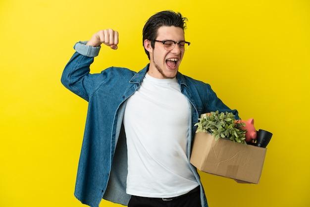 Русский мужчина делает движение, поднимая коробку, полную вещей, изолированную на желтом фоне, делая сильный жест
