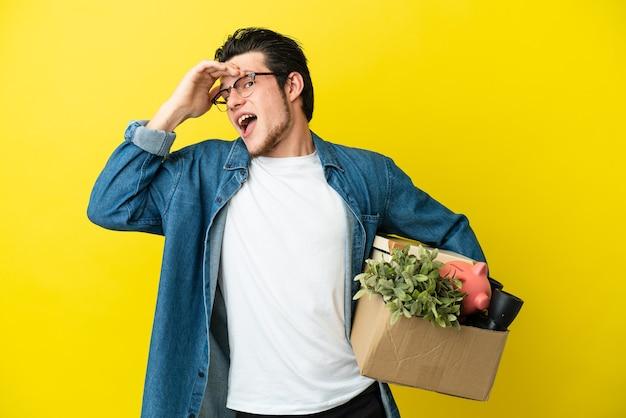 Русский мужчина делает движение, поднимая коробку, полную вещей, изолированную на желтом фоне, делает неожиданный жест, глядя в сторону