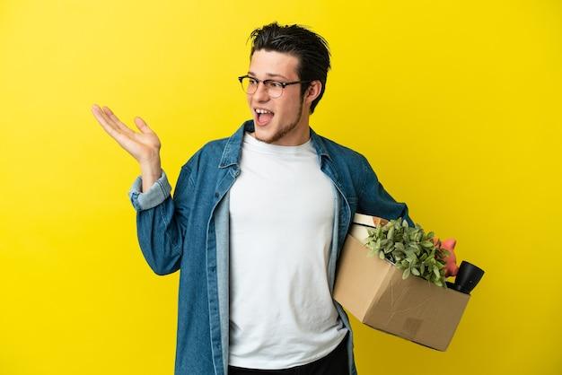 Русский мужчина делает движение, поднимая коробку, полную вещей, изолированную на желтом фоне, протягивая руки в сторону, приглашая прийти