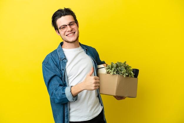 Русский мужчина делает движение, поднимая коробку, полную вещей, изолированную на желтом фоне, показывая большой палец вверх
