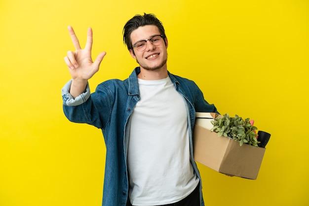 幸せな黄色の背景に隔離されたものでいっぱいの箱を拾い、指で3つを数えながら動きをしているロシア人