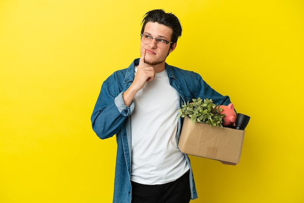 Русский мужчина делает движение, поднимая коробку, полную вещей, изолированную на желтом фоне, сомневаясь, глядя вверх