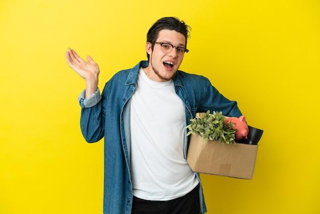 Русский мужчина делает движение, поднимая коробку, полную вещей, изолированную на желтом фоне, сомневаясь, поднимая руки