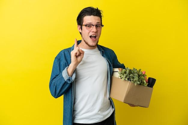 Русский мужчина делает движение, поднимая коробку, полную вещей, изолированную на желтом фоне, намереваясь реализовать решение, подняв палец вверх