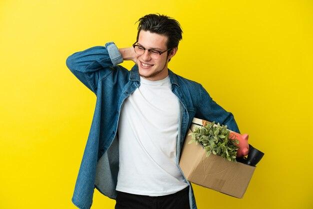 Русский мужчина делает движение, поднимая коробку, полную вещей, изолированную на желтом фоне, смеясь