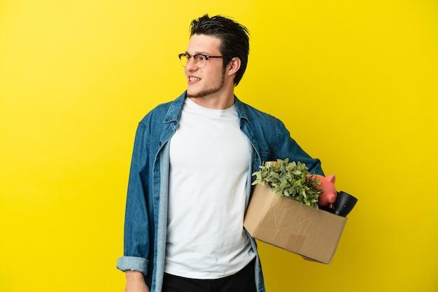 Русский мужчина делает движение, поднимая коробку, полную вещей, изолированную на желтом фоне, глядя в сторону и улыбаясь