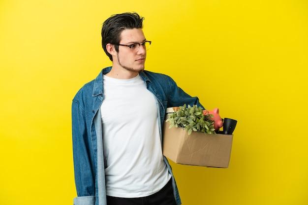 Русский мужчина делает движение, поднимая коробку, полную вещей, изолированную на желтом фоне, глядя в сторону