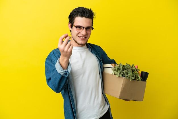 Русский мужчина делает движение, поднимая коробку, полную вещей, изолированную на желтом фоне, делая денежный жест