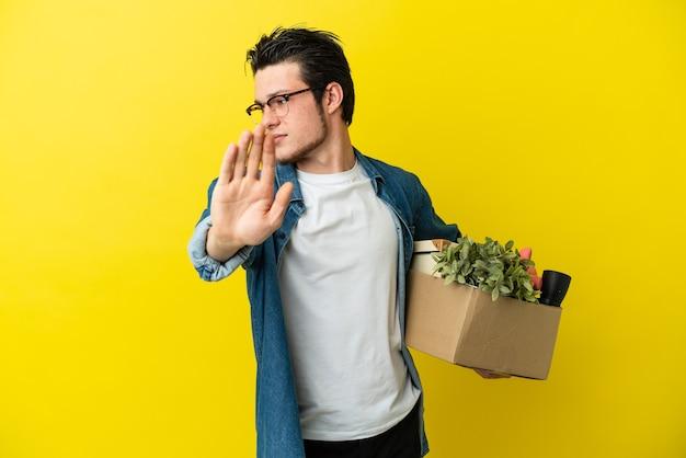 Русский мужчина делает движение, поднимая коробку, полную вещей, изолированную на желтом фоне, делая жест стоп и разочарованный