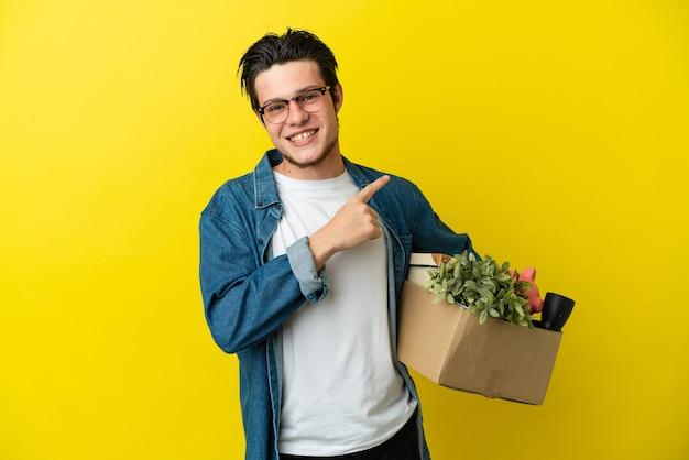 Русский мужчина делает движение, поднимая коробку, полную вещей, изолированную на желтом фоне, указывая в сторону, чтобы представить продукт