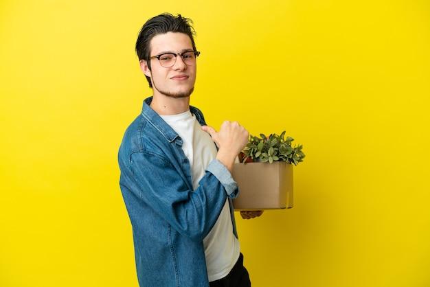 Русский мужчина делает движение, поднимая коробку, полную вещей, изолированную на желтом фоне, гордый и самодовольный