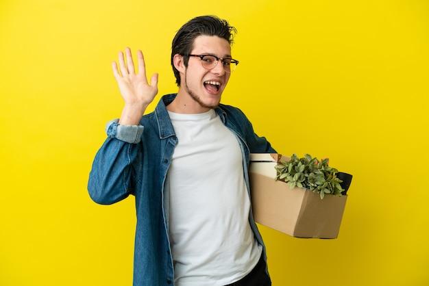Русский мужчина делает движение, поднимая коробку, полную вещей, изолированную на желтом фоне, салютуя рукой со счастливым выражением лица