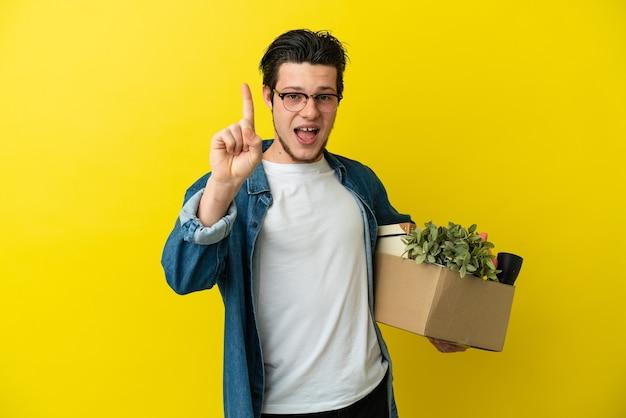 Русский мужчина делает движение, поднимая коробку, полную вещей, изолированную на желтом фоне, показывая и поднимая палец