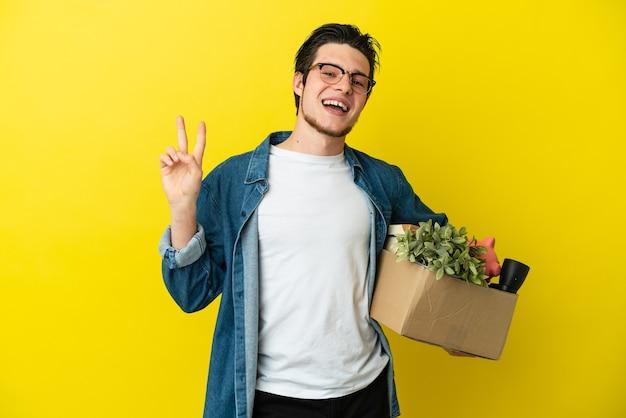 Русский мужчина делает движение, поднимая коробку, полную вещей, изолированную на желтом фоне, улыбаясь и показывая знак победы