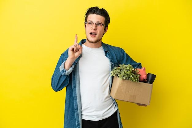 Русский мужчина делает движение, поднимая коробку, полную вещей, изолированную на желтом фоне, думая об идее, указывая пальцем вверх