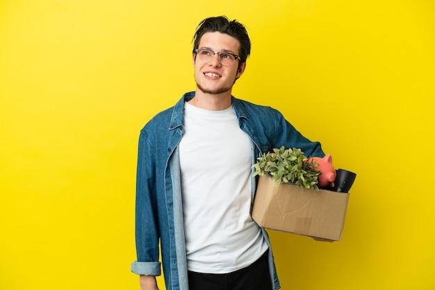 Русский мужчина делает ход, поднимая коробку, полную вещей, изолированную на желтом фоне, думая об идее, глядя вверх