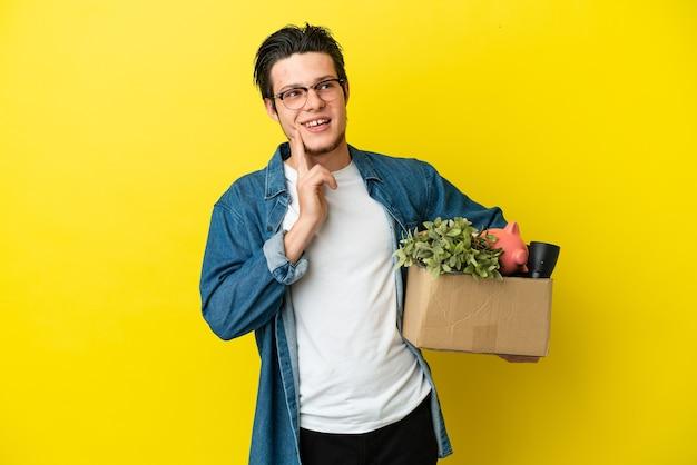 見上げながらアイデアを考えて黄色の背景に分離されたものでいっぱいの箱を拾いながら移動するロシア人男性