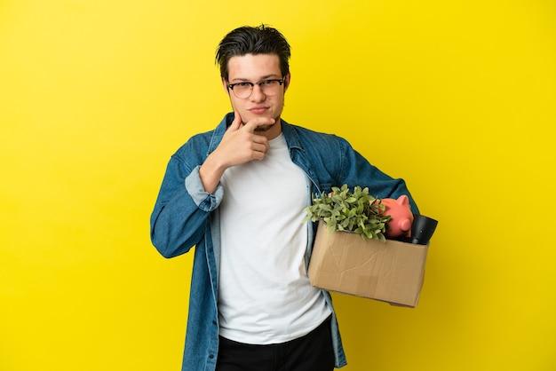 Русский мужчина делает движение, поднимая коробку, полную вещей, изолированную на желтом фоне, думая