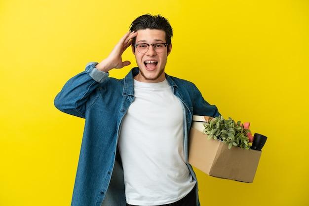 Русский мужчина делает движение, поднимая коробку, полную вещей, изолированную на желтом фоне с удивленным выражением лица