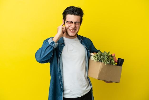 Русский мужчина делает движение, поднимая коробку, полную вещей, изолированную на желтой стене, разочарованный и закрывающий уши