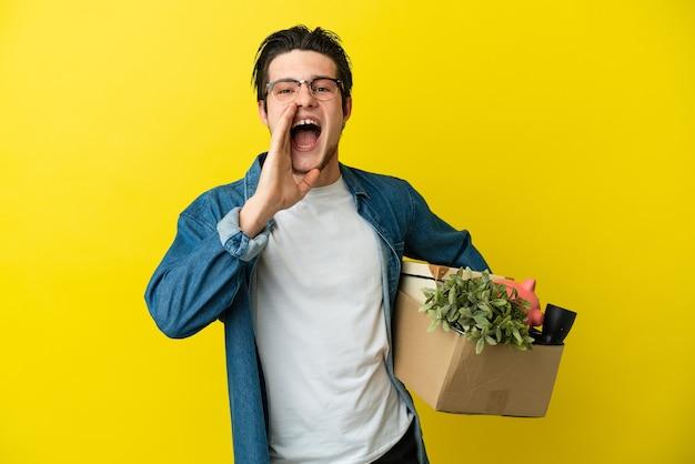 Русский мужчина делает движение, поднимая коробку, полную вещей, изолированную на желтой стене, кричит с широко открытым ртом