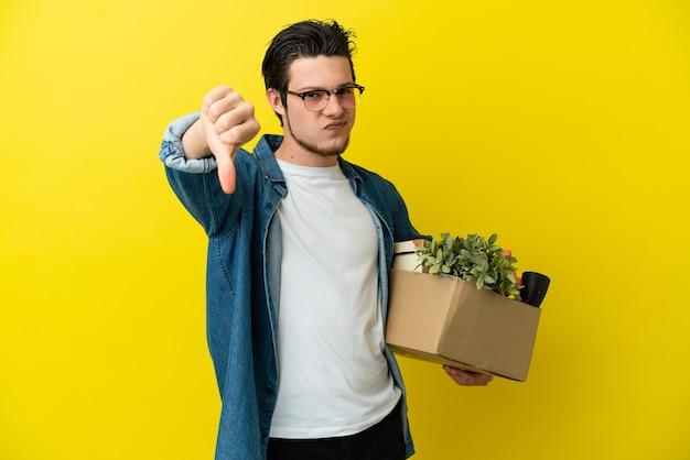 부정적인 표현으로 아래로 엄지 손가락을 보여주는 노란색 벽에 고립 된 것들로 가득한 상자를 집어 들고 움직이는 러시아 남자