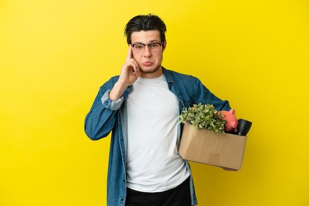 Русский мужчина делает движение, поднимая коробку, полную вещей, изолированную на желтой стене, обдумывая идею