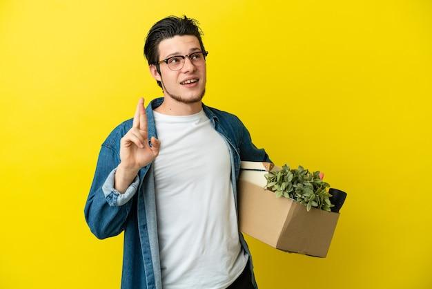Русский мужчина делает движение, поднимая коробку, полную вещей, изолированную на желтой стене, скрестив пальцы и желая всего наилучшего